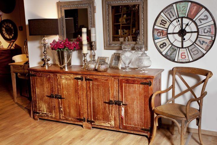 Masywna komoda w starym stylu. Drewniany mebel, który nosi na sobie ślady czasu w postaci przetarć i przejaśnień. Designerskie uchwyty komody przypominają stare zapięcia do walizek.