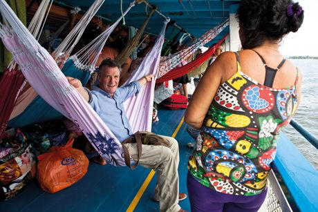 Micheal palin travelling on the amazon on a ferry with hammocks