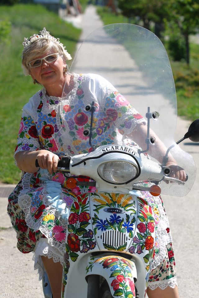 Kalocsa Folk Art ― Beautifuly and creatively applied Hungarian embroidery design to both the dress as well as the Scarabeo white scooter. #Budapest  #Kalocsa #Scarabeo
