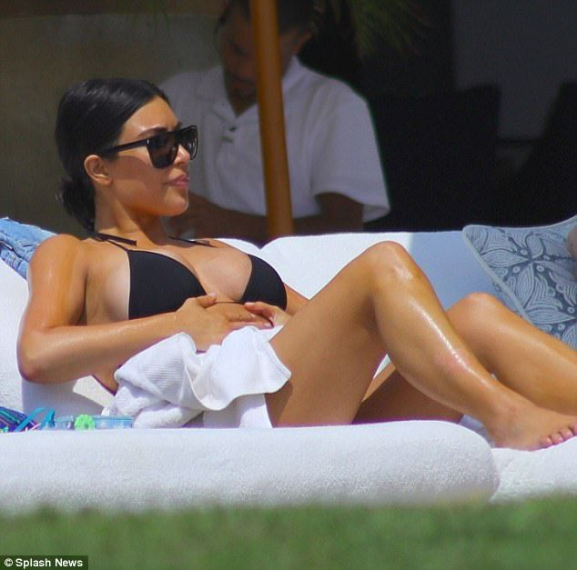 The 36-year-old highlighted her famous curves in another barely there beach look. She slipped on high-cut black bikini bottoms with a lace up crop top during her Mexico holiday.