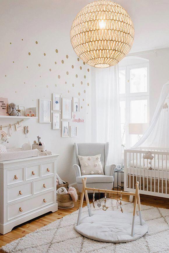 Une chambre bébé avec un tapis berbère et une suspension en rotin ...