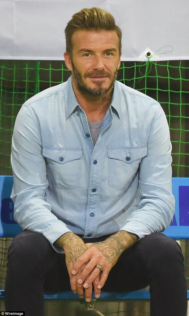 Stylish: Watching from the sidelines, David wore a pale denim shirt over a grey top with d...