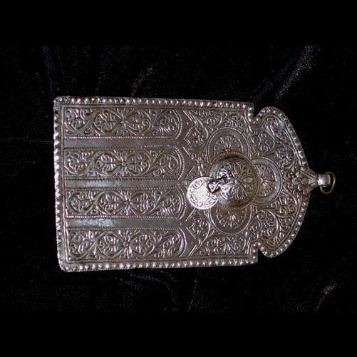 """Silver """"door"""" pendant, carved floral motifs. Acentral eye (protective symbol) carries a small silver coin.  The """"louha"""" (which takes its name from its flat shape) was worn by women of the southern tribes Morocco.  It was worn around the neck, or on the belt.  The louha presented is done in the engraving style typical of Marrakech.  - circa 1920  Marrakech - vers 1920"""