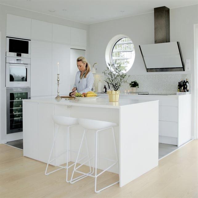Vitt kök. Det vita köket från Tibro kök smälter in fint och för att få en detalj som sticker ut valde familjen att ha mosaik med inslag av marmor från Bricmate. Fläkt från Fjäråskupan. Barstolar från Hay.
