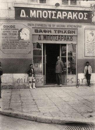 Φωτογραφία από την αθηνα του 1910. Το διάσημο κομμωτήριο στη Σταδιου στη στοά Αρσακειου. Το όνομα Μποτσαράκος ήταν συνώνυμο της βαφής των μαλλιών αλλά και των υπερήφανων μουστακιών. Ο εν λόγω χρησιμοποιούσε την πρώτη εγκριθείσα υπό του Βασιλικού Ιατροσυνεδρίου Βαφή Τριχών Δ. Μποτσαράκου και εφάρμοζε το τελειότερον σύστημα διά να βάφη στιγμιαίως την κόμην, τον μύστακα και το γένειον. Υπήρχε διάρκεια εγγυημένη 40 ημερών διά τους άνδρας και δύο μήνας δια τας Κυρίας. Πηγή: mikros romios.gr