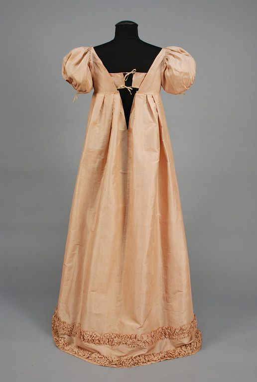 LOT 623 SPANISH QUEEN'S STRIPED SILK DRESS, c. 1810. White and pale red having high waist and short puffed sleeve, slightly trained skirt, the hem decorated with a double row of pinked and ruched self fabric, unusual back closing, possibly originally covered by a train, belonged to the Queen Consort of Spain and the Indies, nee Marie Julie Clary. B-36, high W-30, L 52 1/2-55 1/2. (Small mend at top of shoulder, few small, light stains) excellent.