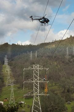 Pacific Gas and Electric Company work the power lines near the base of the spillway at Lake Oroville in Oroville Calif.   Brian Baer/ California Department of Water Resources