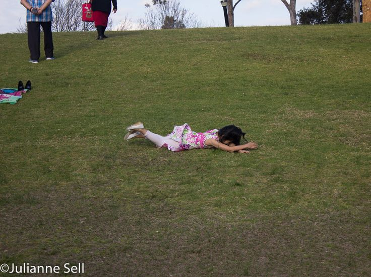 L1M2AS3 Frozen action of a young girl rolling down the hill - Canon 600D, aperture f/5.6, shutter 1/320, ISO 200, 55mm focal......Issy OC Trainer 'Rumbly-tumbly' - great game and lots of fun, freeze motion, aim to frame up without distracting elements, the horizon is quit give to include as it gives the action context.