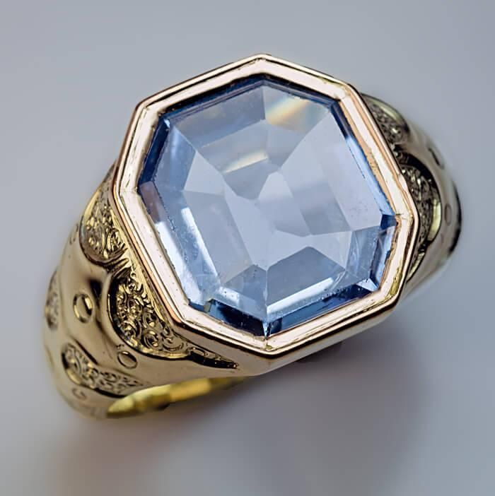 St. Petersburg 1870s A heavy 14K gold men's ring chased with stylized medieval designs in Neo-Russian style is bezel-set with a pale blue octagonal