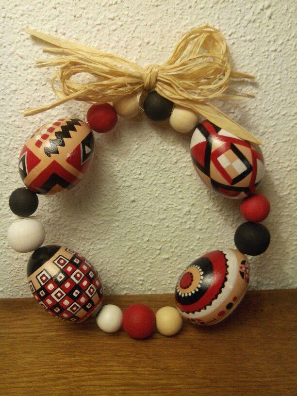 Couronne réalisée avec 4 oeufs de poule et des perles en bois assemblés sur un fil de fer. Le tout est fermé par un noeud en raphia naturel