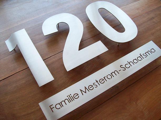 Huisnummers uit losse cijfers met een bijpassende naamplaat. Zeer luxe uitstraling.