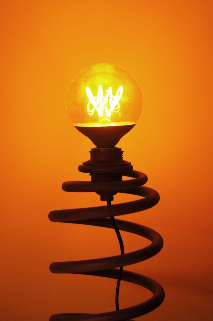 """Lampa wykonana z części samochodowych: sprężyny oraz tarczy hamulcowej jako podstawy. Całość pokryta chropowatym lakierem imitującym rdzę. Dane techniczne: - wysokość 46 cm, - średnica tarczy 23,5 cm, - waga 4,7 kg, - dł. kabla 162 cm, - żarówka """"edisonka"""" typu LED, o mocy 4W"""