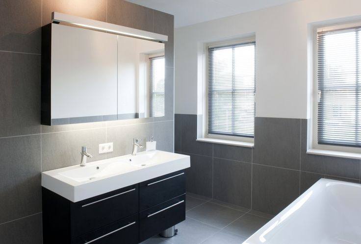 Tijdloze badkamer met dubbele wastafel en grote spiegel.