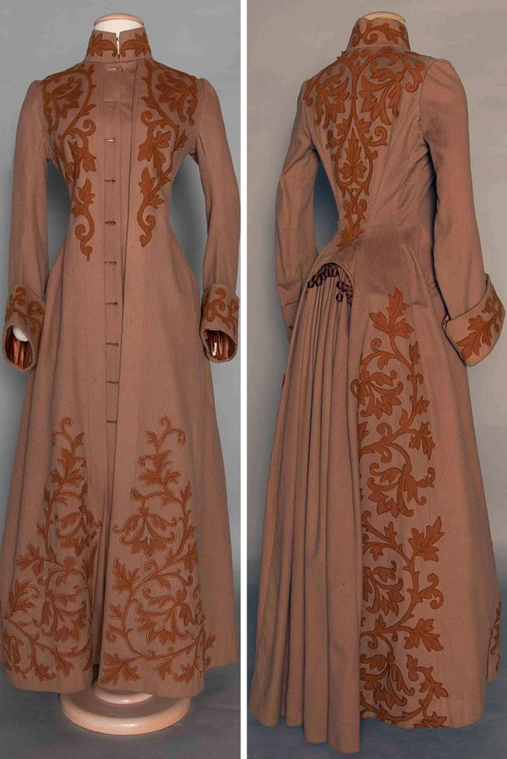 Appliquéd wool bustle coat ca. 1888. Cocoa brown with chestnut wool leaf and scroll appliqués, and high band collar. Long fitted sleeves widen to deep cuffs, back fitted with gathered panel for bustle trimmed with baubles. Augusta Auctions
