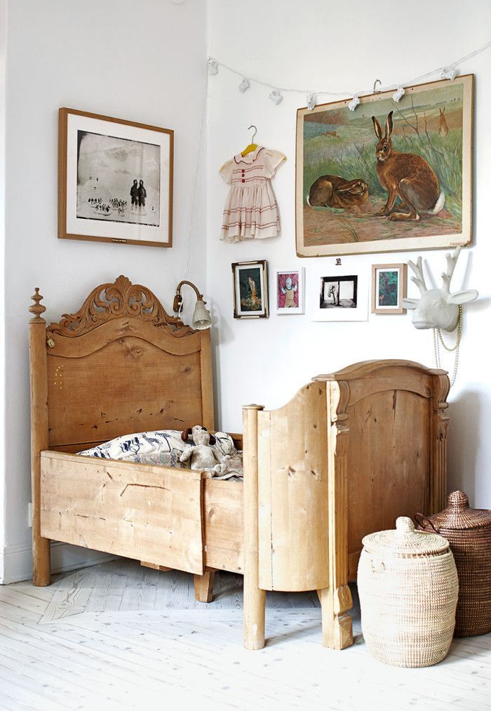 ADORABLE antique bed and wall art in little girls room with small baskets at the foot of the bed