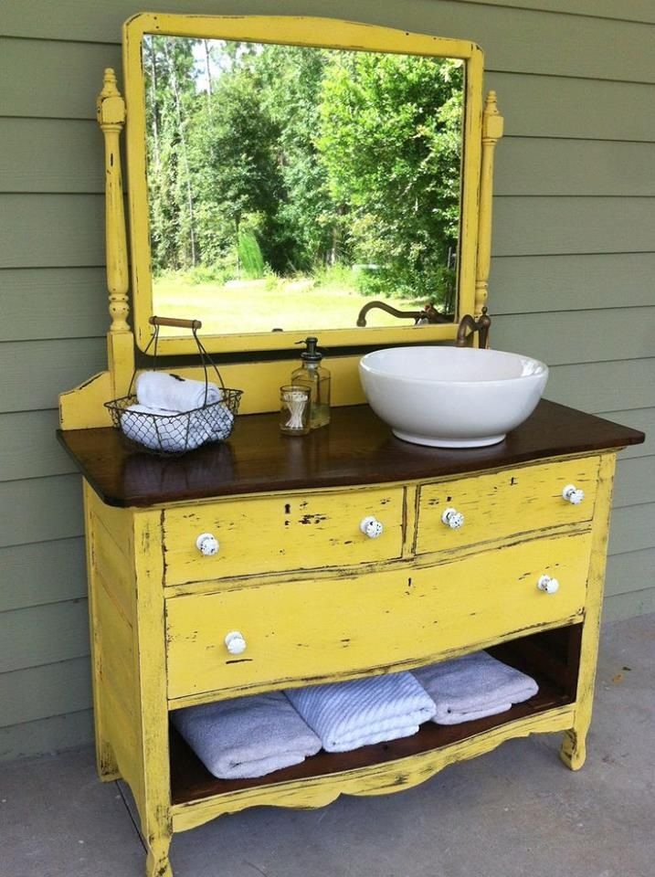 Vintage dresser becomes a bathroom vanity complete with white porcelain vessel sink, offset to one side to give more counter space. Note the bottom drawer has been removed for open shelf towel storage.