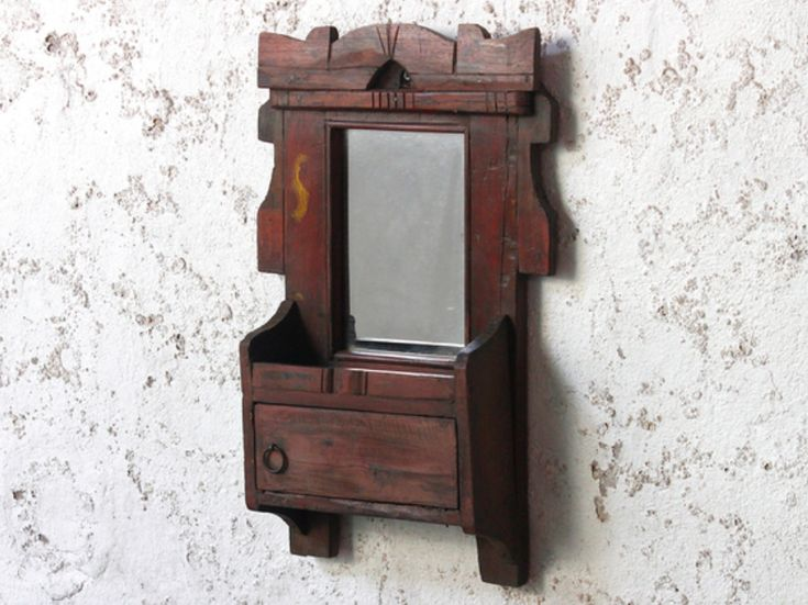 A rustic traditional ornate wall mirror with decorative etched detailing and a small storage space accessed through a cute door. #vintage #mirror #unique #furniture #homedecor #homestyle
