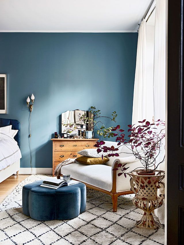 Blue wall and daybed in the bedroom of the beautiful Stockholm home of  Amelia Widell -