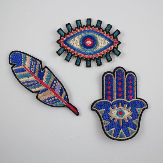 "Hamsa Patch, Iron On Patch, Embroidered, Patches, Iron On, Applique, Blue, Evil Eye, Wildflower + Co. DIY ------------------------------------------------ Show off your spiritual side with this talisman believed to provide protection. 100% embroidered in shades of blue, vibrant pink & neutrals. Wildflower + Co. patches are the perfect instant update! Patches feature an iron-on backing & ship with instructions.  • Measures approx. 2 ¼"" high x 1 ¾"" wide • Designed by & exclusive to Wildflower…"