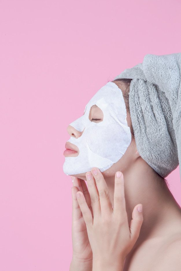 Beautiful asian women are using face mask face on sheet on a pink background. Free Photo