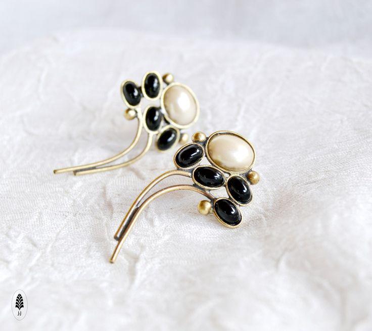Černá s perletí. Náušnice v černo - bílé s rostlinným motivem, elegantní nadčasový styl. Vytvořené jako levá a pravá do ucha na titanový dřík a gumovou zarážku. Dlouhé 2,7cm. Vyrobeno za pomocíklasických zlatnických a pasířských technik, a lepenímskleněných kamenů.Šperk jepatinovanýdo podoby starobronzu a nakonecjemně přelakovaný. oTombak je ...