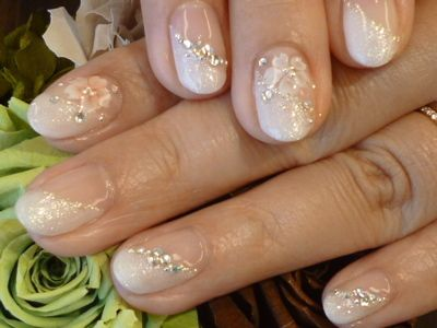 Delicate Swarovski crystal-encrusted nails with cherry blossoms.