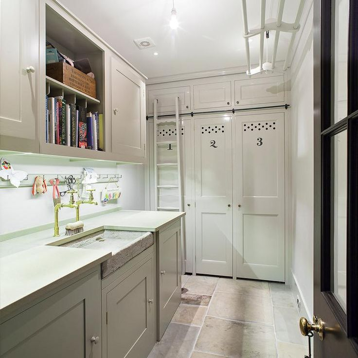 Laundry room and mudroom combo features gray cabinets paired with gray countertops fitted with a shallow concrete sink and two spigot faucets situated under a an open bookcase flanked by cabinets.