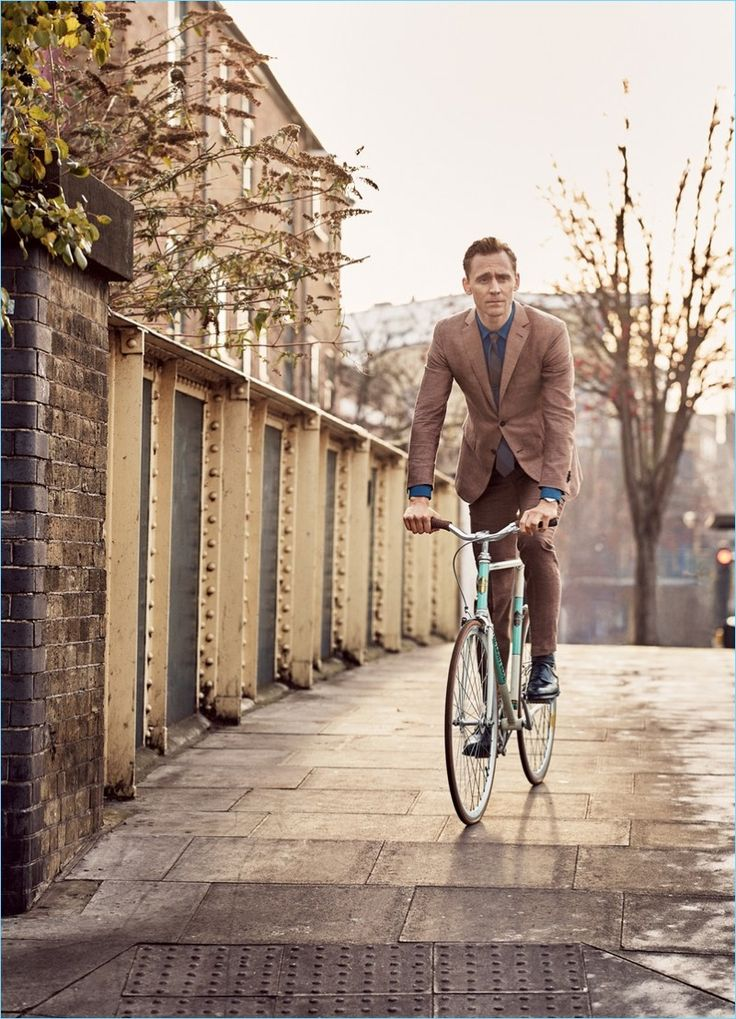 Taking a bike ride, Tom Hiddleston wears an Ermenegildo Zegna suit, shirt and tie with To Boot New York shoes.