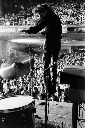 "Unpublished. Jim Morrison leaps on stage during a Doors concert at New York's legendary but short-lived Fillmore East. ""Our live concerts are totally different from our records,"" Doors drummer John Densmore told the LIFE writer at the time. ""I mean, it's theater."""