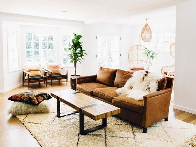 Bohemian inspired living space with a leather sofa, and a large Morrocean area rug