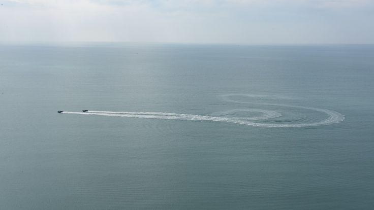 Boats exploring the Jurassic Coast at Golden Cap, Dorset, England