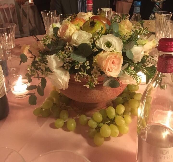 Centrotavola matrimonio con coccio in terracotta con melograno e uva con fiori dai toni pastello per un effetto rustico chic