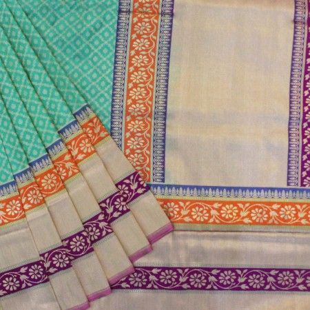 Lovely teal green base banarasi saree has floral and paisley motif jal all over. The border and pallu has floral bel in orange and purple base, narrow gold zari stripes along with thin stripes of tree motif.