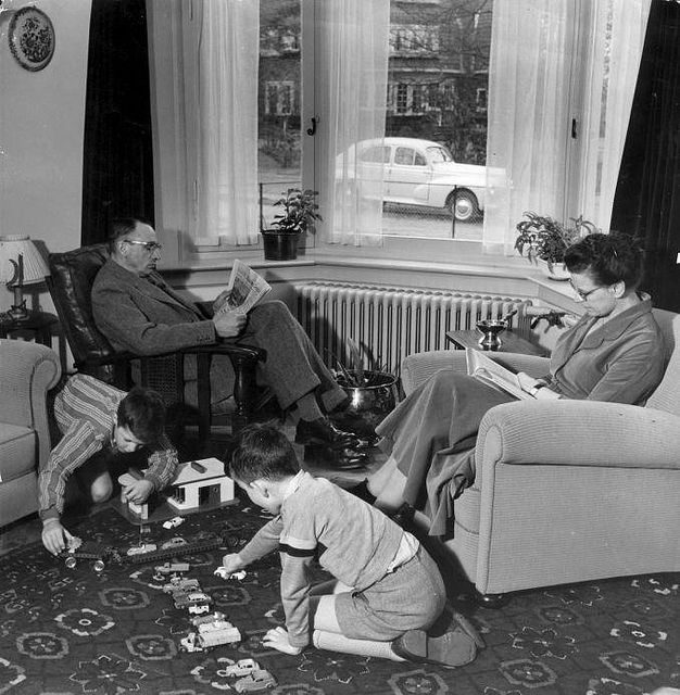 Dutch family in the fifties. Father and mother reading while the children are playing in the living room. The Netherlands, 1956.