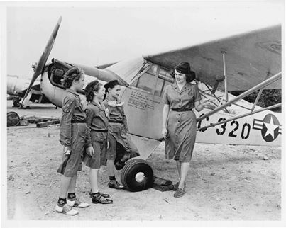 A Girl Scout Wing Scout stands in front of a single engine Piper Cub style airplane with three Intermediate Girl Scouts, circa 1940s. #ThrowbackThursday