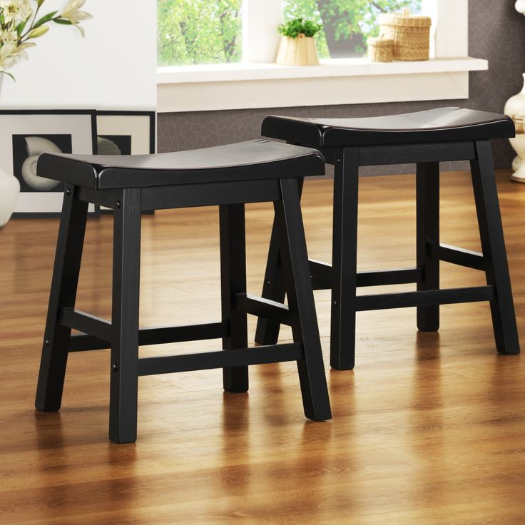 Add extra seating and a definite sense of style to any room in your home with these black saddle seat stools. This set of two 18-inch wood stools with a black finish is hand distressed so you get that worn-in feel right out of the box.