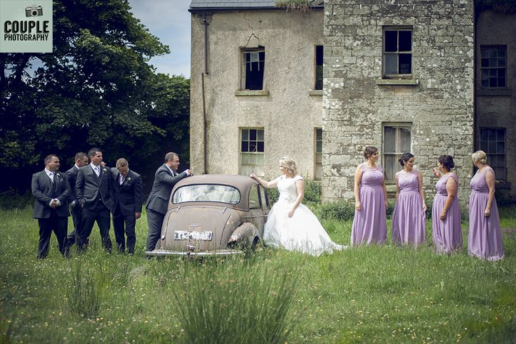 The bridal party outside an old historical house and old car. Weddings in Mayo, Photographed by Couple Photography.