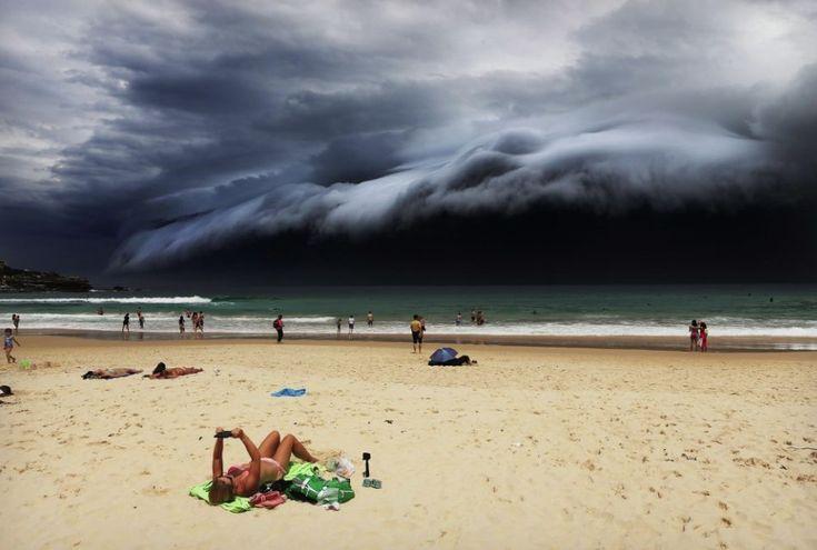 Rohan Kelly, Australia, 2015, Daily Telegraph, Storm Front on Bondi Beach    Chmury tsunami docierające nad Sydney. Zdjęcie zdobyło 1. Nagrodę w kategorii Nature. Kobieta na plaży zdaje się nie przejmować chmurą nad Bondi Beach w Sydney. Zdjęcie wykonano 6 listopada 2015.