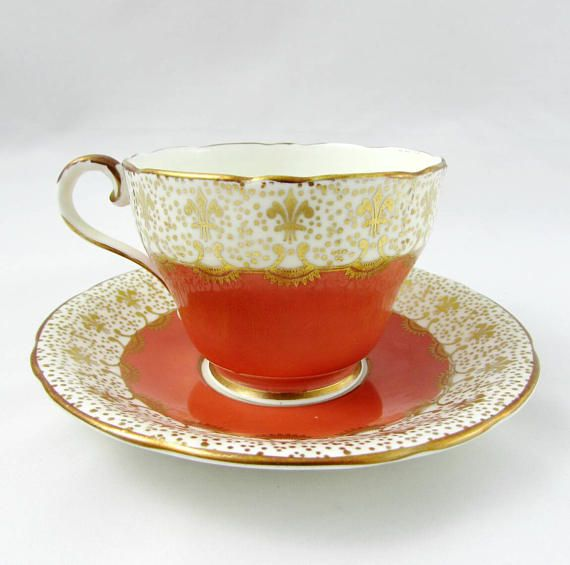 Orange Aynsley tea cup and saucer with purple flowers on the inside rim of the teacup. Gold trimming on the edges of tea cup and saucer and on the handle. Excellent condition (see photos). Markings read: Bone China Aynsley England For more Aynsley tea cups, please click here: