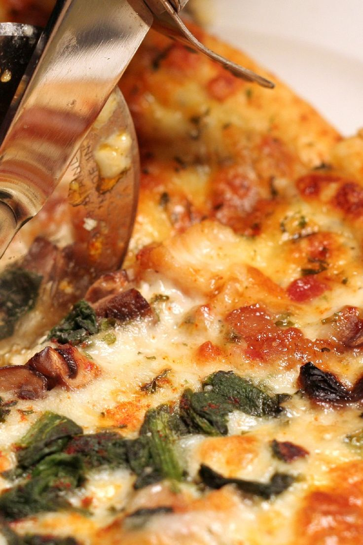 Recipe including course(s): Entrée; and ingredients: mozzarella cheese, mushrooms, olive oil, pre-baked pizza crust, sesame oil, spinach