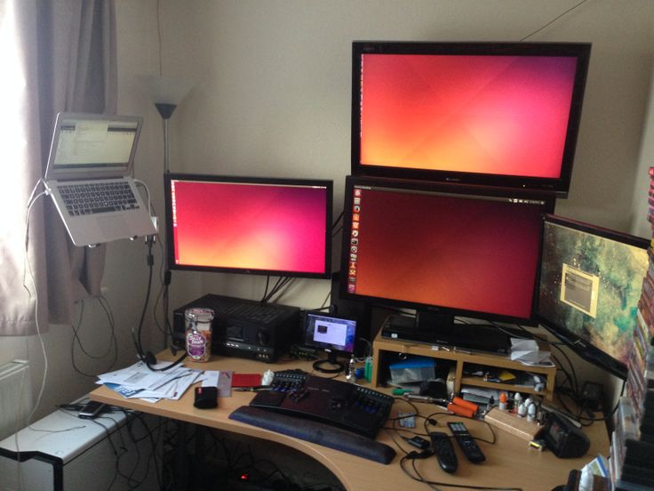 Canonical dev Michael Foord's workspace. Ubuntu 14.04 with three monitors, MacBook Air running an external monitor plus USB monitor, Sony A/V receiver running 7.1 sound, Kinesis Advantage keyboard and Evoluent vertical mouse.
