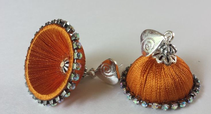 This is a silk thread jhumka in festive orange color.