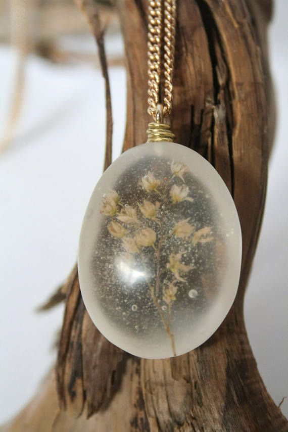 Pressed and dried white and green wildflowers grown and harvested on the West coast of BC, encased in a clear oval-shaped, resin pendant. All pieces are made one at a time and entirely by hand, embedded with locally sourced objects. Each piece is sanded from 220 to 3000 grit and