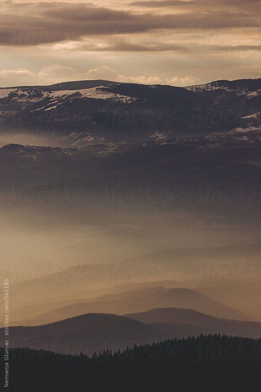 Peaceful sunset with sun rays cutting through layers of fog over mountain Kopaonik in Serbia.  You can license this photo exclusively at Stocksy United.