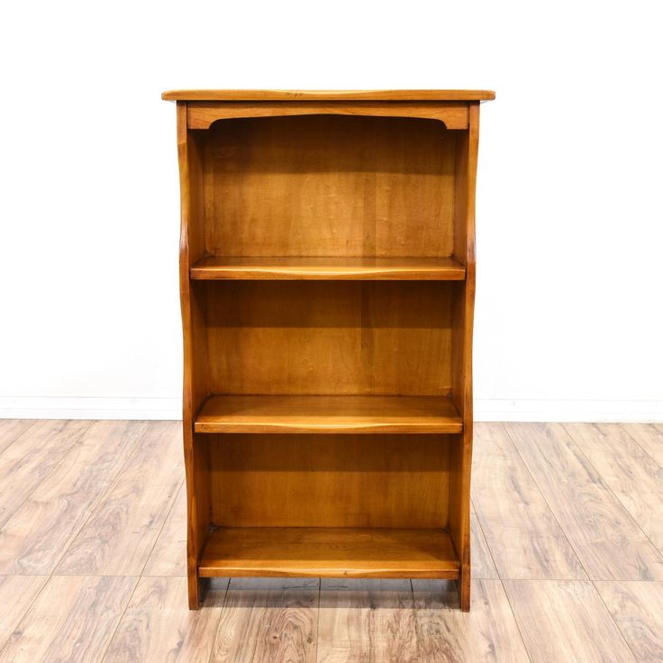 This bookcase is featured in a solid wood with a glossy maple finish. This country style bookshelf has curved trim, 3 shelves and sturdy feet. Perfect for organizing books and movies! #countryfarmhouse #storage #bookcase&shelving #sandiegovintage #vintagefurniture