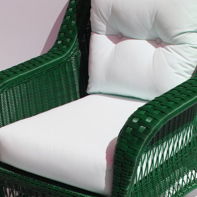 wicker chair in green up close with sunbrella natural cushions green