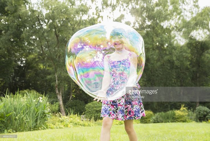Père et fille jouant avec des bulles dans le grand jardin