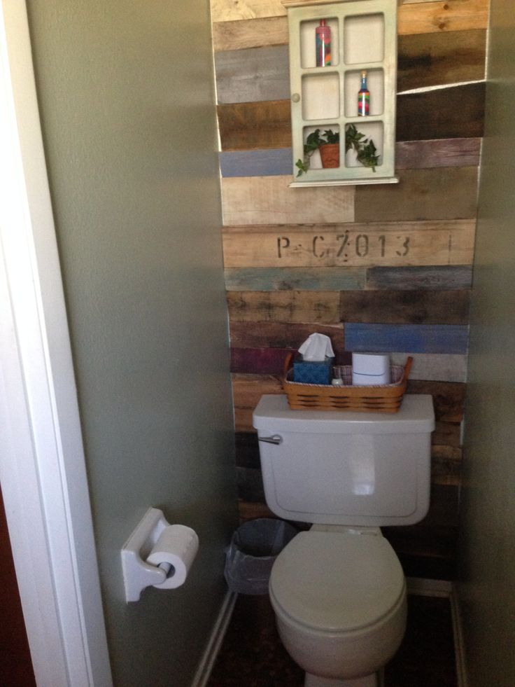 pallet wall behind toilet with green paint