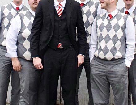 Groomsmen sweater vest; groom in suit.