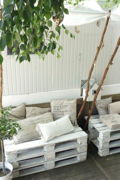 Terrasse d'été improvisée avec des palettes peintes en blanc et quelques coussins de couleur beige et crème